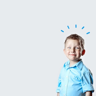 A smiling happy boy in blue shirt on light background