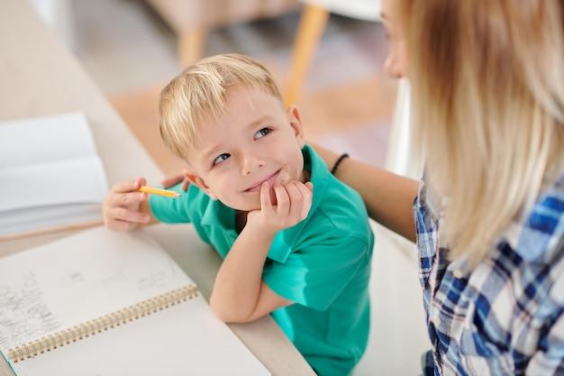 Улыбающийся счастливый мальчик смотрит на мать, объясняя сложную математическую тему
