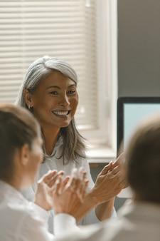 Улыбаясь счастливый предприниматель на встрече в офисе группы. работающая женщина в чате в компьютерном приложении или