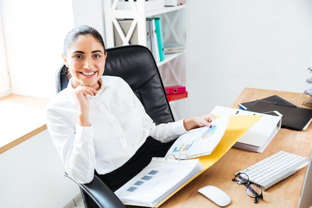 Улыбаясь счастливая бизнесвумен, держащая отчеты и смотрящая вперед, сидя на рабочем месте