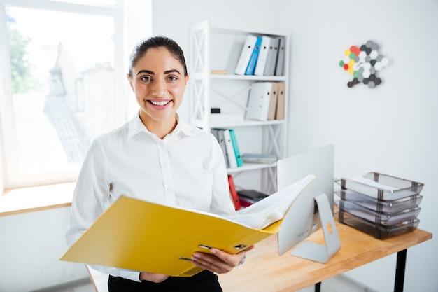 Улыбаясь счастливая бизнесвумен, сидящая на столе с документами в офисе и смотрящая на фронт