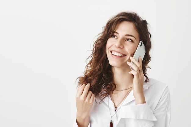 Улыбается счастливая деловая женщина разговаривает по телефону и смотрит в левый верхний угол