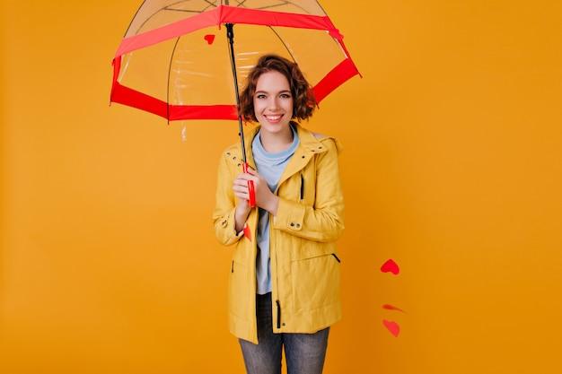 Ragazza caucasica felice sorridente che tiene parasole rosso sulla parete gialla. foto dell'interno di graziosa giovane donna con i capelli ondulati in piedi sotto l'ombrello.