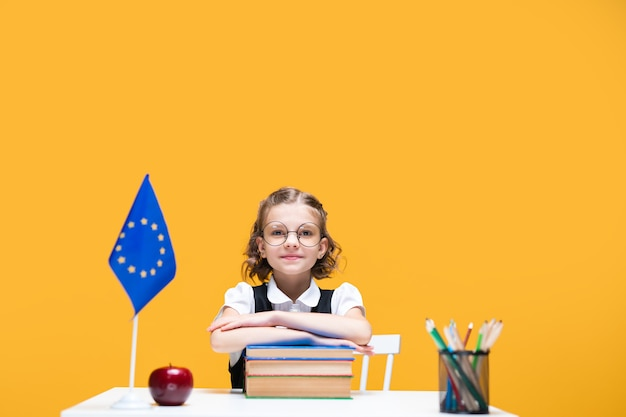 Smiling happy caucasian schoolgirl sitting at the desk with books english lesson european union flag