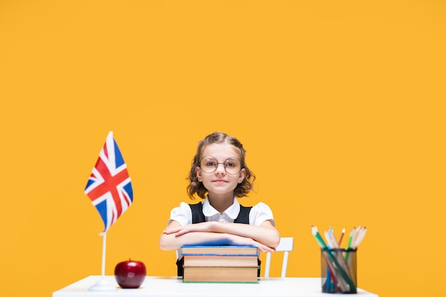 Smiling happy caucasian schoolgirl sitting at the desk with books english lesson great britain flag