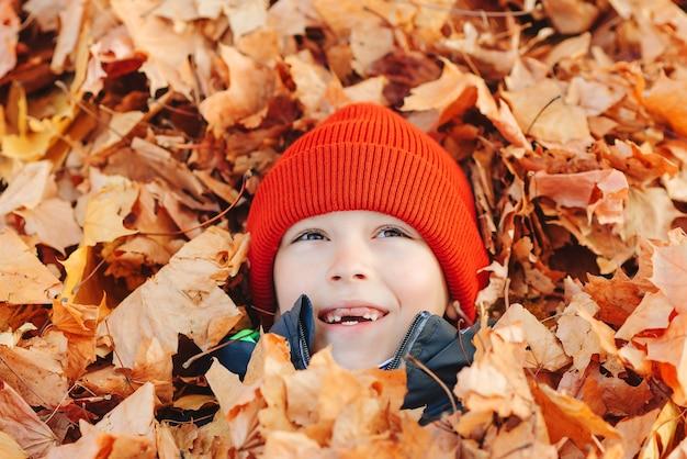 Улыбающийся счастливый ребенок, отдыхающий в осенних листьях. мальчик играет с опавшими кленовыми листьями.