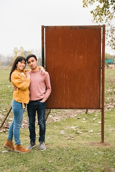 Smiling happy couple in denim in countryside next to metal rusty stand