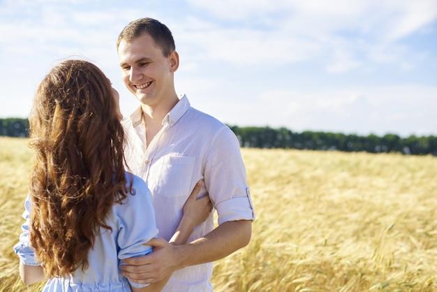 Улыбаясь счастливая пара. красивый кавказский парень в белой рубашке нежно обнимает улыбающуюся девушку со светлыми волосами в платье.