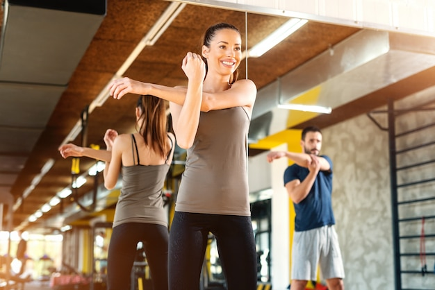 Smiling happy couple stretching arms while standing in gym in front of big mirror.
