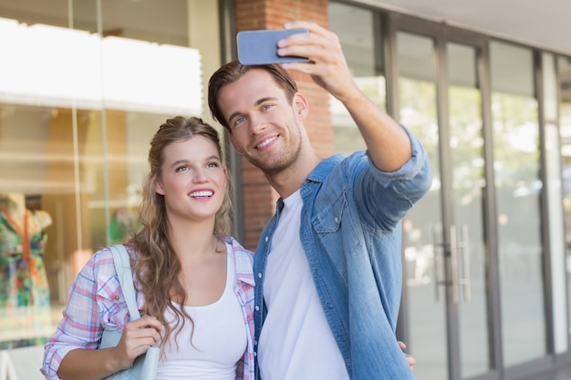 A smiling happy couple taking selfies
