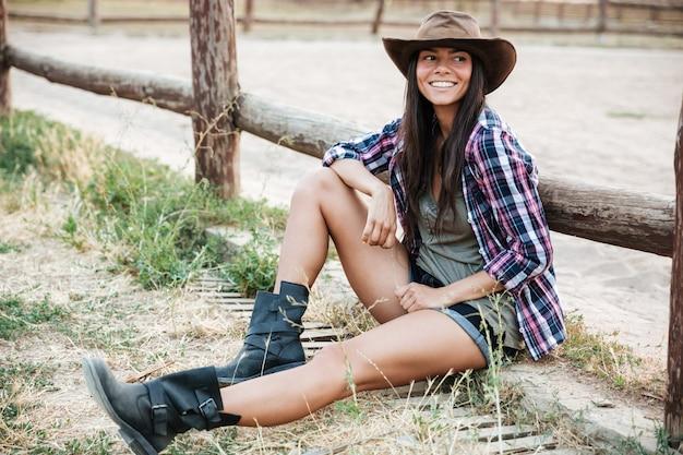 牧場の柵で座って休んで帽子をかぶって幸せな騎乗位の笑顔