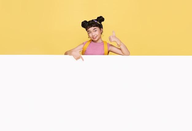 노란색 배경에 격리된 빈 화이트 보드 뒤에 숨어 있는 행복한 귀여운 아시아 아이가 웃고 있습니다.