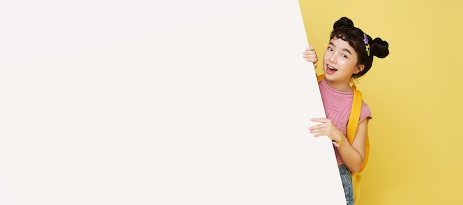 黄色い壁に隔離された空白のホワイト ボードの後ろに隠れて笑顔のかわいいアジアの子供。
