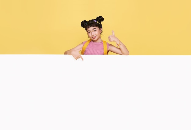 Smiling happy cute asian child hiding behind a blank white board isolated on yellow background.