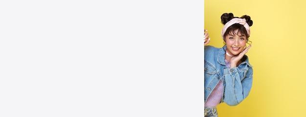 노란색 배경에 격리된 빈 화이트 보드 뒤에 숨어 있는 행복한 귀여운 아시아 소녀가 웃고 있습니다.