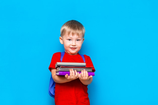 バックパックと幸せなかわいい賢い少年の笑顔。彼の手に本の山を持つ子供。学校の準備ができて学校に戻る