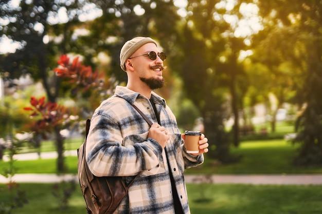 세련된 남자의 웃는 행복한 얼굴은 휴식 시간을 가지면서 커피와 함께 야외 공원을 산책합니다.