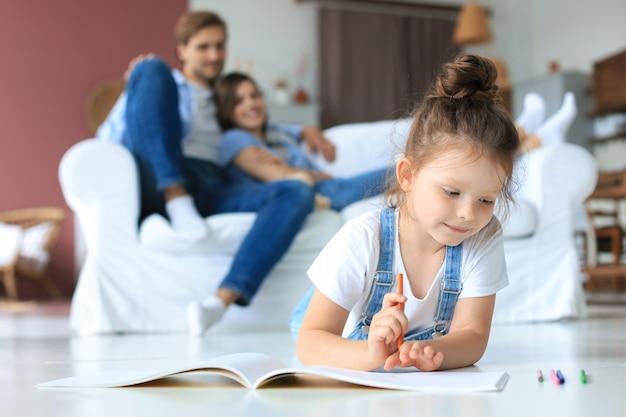 笑顔の幸せな家族は、リビングルームのソファでリラックスして座って、小さな娘がカラフルな鉛筆でアルバムを描いているのを見てください。家で幸せな週末。