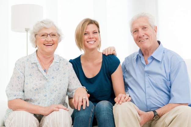 Улыбающаяся счастливая семья с внучкой, бабушкой и дедушкой