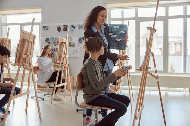 Улыбающаяся счастливая учительница смешанной расы смотрит на рисунок ученика