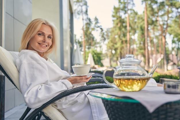 손에 차 한잔 들고 해먹이에 앉아 웃는 행복 한 여성