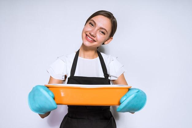 笑顔の幸せな女の子はオーブンでおいしいパイを焼いた黒いエプロンで調理します