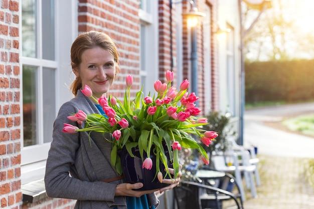 伝統的なオランダの家の近くにピンクのチューリップの花瓶を持って笑顔の幸せな女の子。オランダ