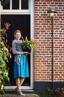 ピンクのチューリップと花瓶を保持している幸せな女の子の笑顔