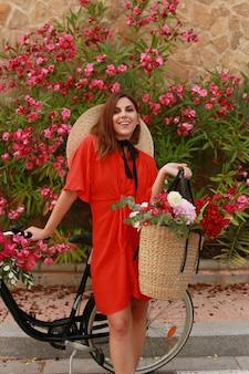 街の通りにレトロな自転車でドレスと帽子で笑顔の幸せな女の子
