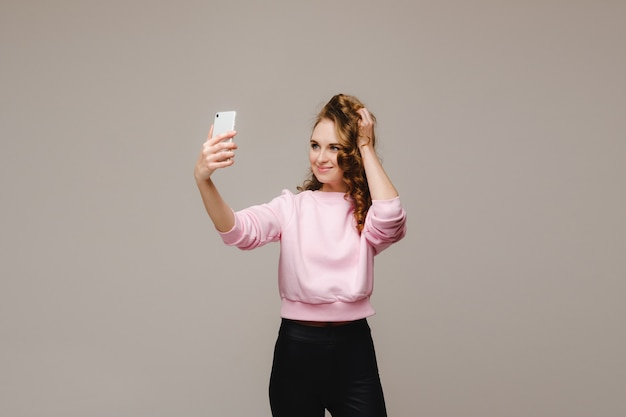 A smiling happy girl in a pink blouse takes a selfie on a smartphone on a gray background