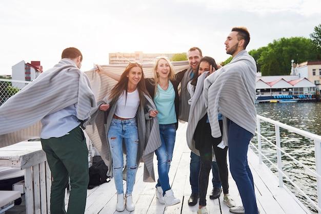 Улыбаясь счастливая группа друзей, позирующих на открытом воздухе на пирсе пляжа.