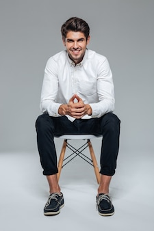 Улыбающийся счастливый красавец в белой рубашке сидит на стуле над серой стеной