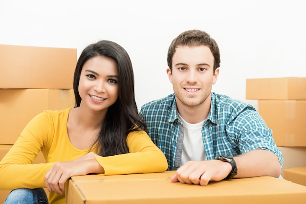 Smiling happy interracial couple just moving into new house