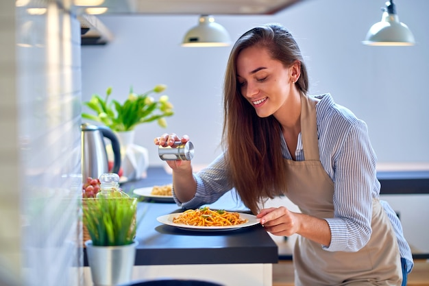 Smiling happy joyful cute cooking woman housewife salts and prepares a food for dinner