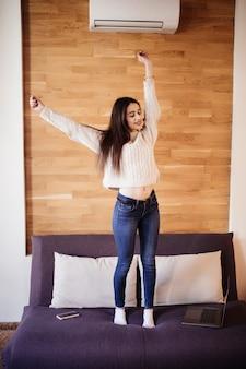 Signora felice sorridente lavora a casa allungando le braccia per rilassarsi dopo una dura giornata