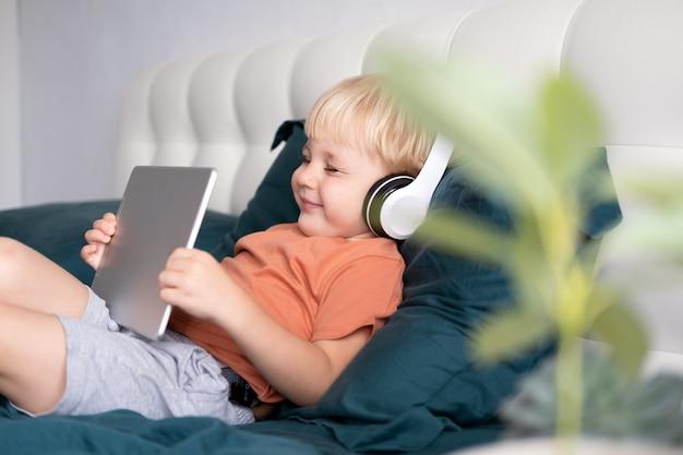 自宅のベッドでワイヤレスヘッドフォンでタブレットを使用して幸せな小さな男の子の笑顔。