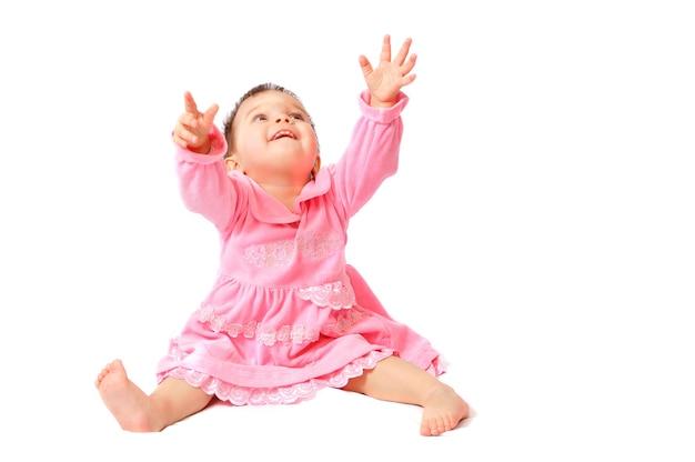 手を上げて座っているピンクのドレスで幸せな小さな1歳の女の赤ちゃんを笑顔。
