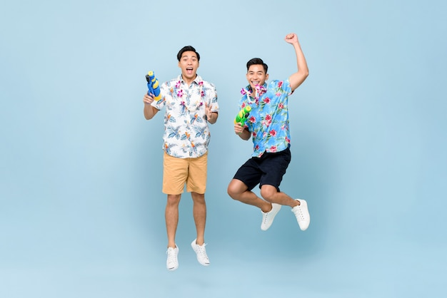 Smiling happy male friends playing with water guns and jumping for songkran festival in thailand and southeast asia