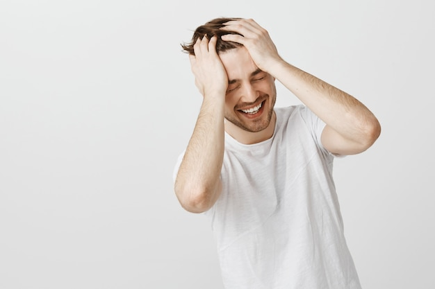 Улыбающийся счастливый человек не может поверить в свою удачу, держась за голову и смеясь