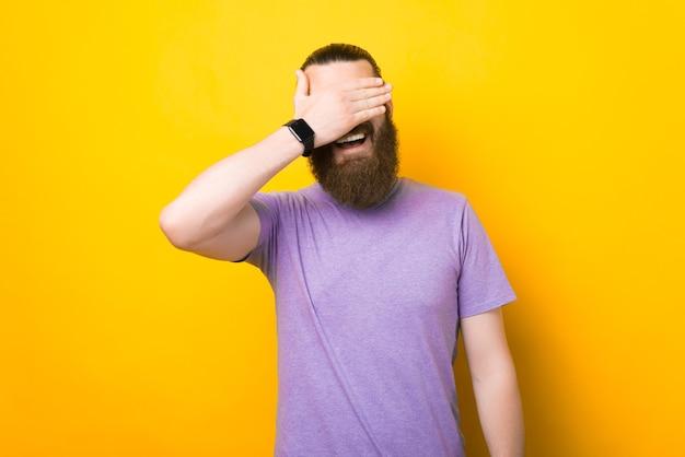 Улыбающийся счастливый человек закрывает глаза рукой.