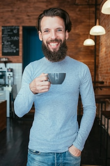 Smiling happy man standing in coffee shop holding cup of hot drink