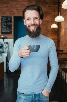 Улыбающийся счастливый человек, стоящий в кафе, держа чашку горячего напитка