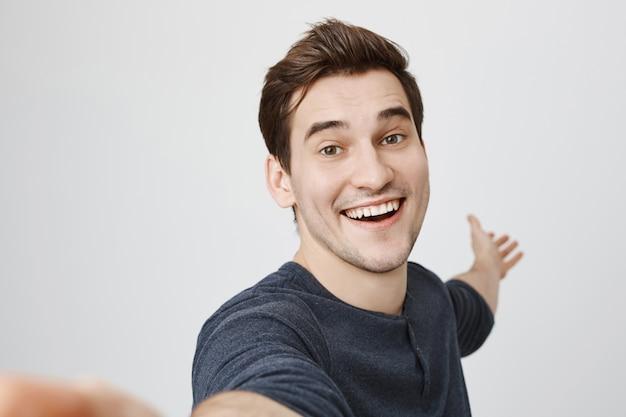 Sorridente uomo felice prendendo selfie e puntando la mano