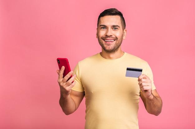 スマートフォンとプラスチックのクレジットカードを保持しているカジュアルなtシャツを着て幸せな男の笑顔