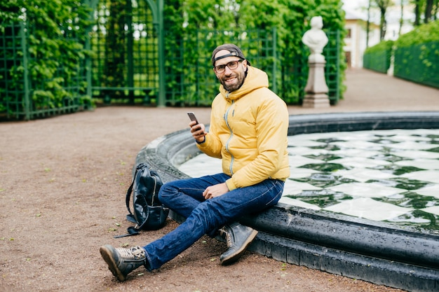Smiling happy man with bristle wearing casual clothes and big eyewear sitting crossed legs near fountain in park holding