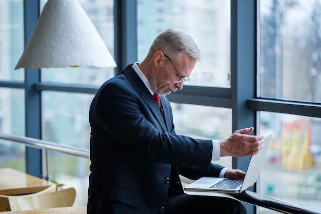 웃고 있는 행복한 전무 이사는 복사 공간이 있는 창 배경 근처에 있는 사무실에서 노트북과 함께 서 있는 동안 그의 성공적인 경력 개발에 대해 생각합니다