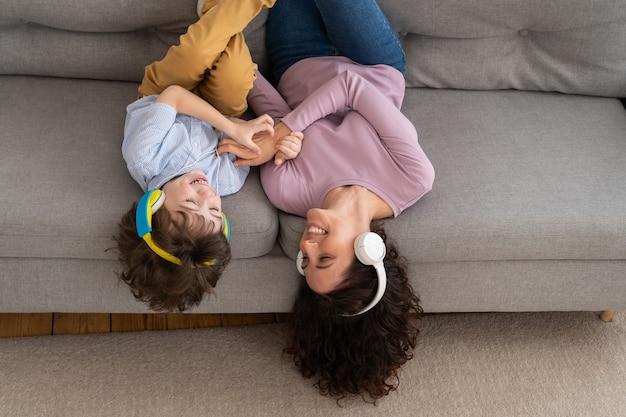 웃는 행복 한 엄마와 아이가 집에서 소파에 누워
