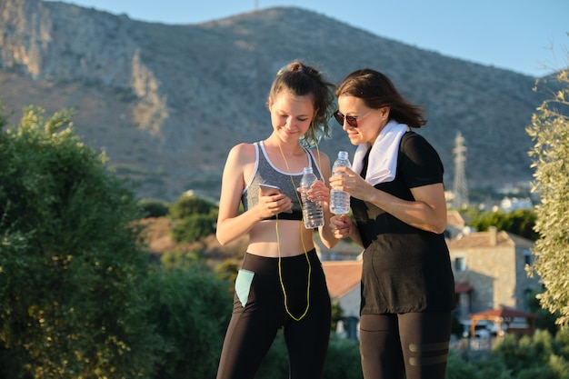 Smiling happy mother and daughter teenager relaxing after exercise drinking water and looking at smartphone