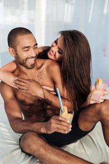 행복 한 다민족 부부 침대에 앉아 해변에서 마시는 미소