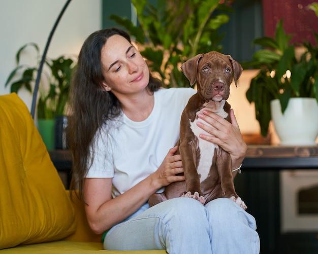 Улыбающийся счастливый владелец домашнего животного смотрит на щенка американского питбультерьера, сидящего на коленях в жизни